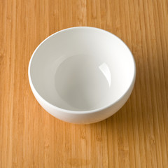 white empty bowl on a bamboo table top