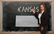 Teacher showing map of kansas on blackboard