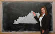 Teacher showing map of kentucky on blackboard