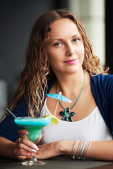 Happy young woman with cocktail at restaurant