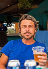 Summer man with blonde hair drinking a beer. Blue shirt.