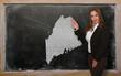 Teacher showing map of maine on blackboard