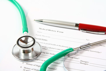 Green stethoscope and a red pen lying on a medical history form