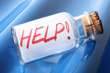 "An artistic concept of a bottle with a message ""help"""