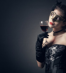 woman in carnival mask and a glass of red wine.