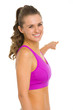 Portrait of smiling fitness young woman pointing on copy space