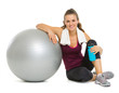 Happy fitness woman sitting near fitness ball after workout