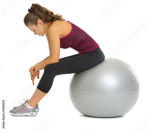 Tired fitness young woman sitting on fitness ball