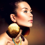 Fashion Woman Portrait. Golden Jewels. Trendy Makeup