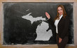 Teacher showing map of michigan on blackboard