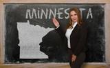 Teacher showing map of minnesota on blackboard