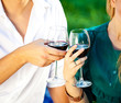 couple holding a glass of red wine in the garden