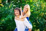 young couple having fun piggybacking in park