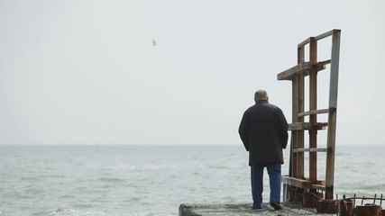 Lonely elderly man walking on the beach
