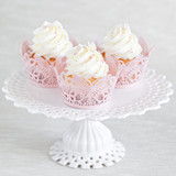 Cupcakes with vanilla cream on cake stand, selective focus