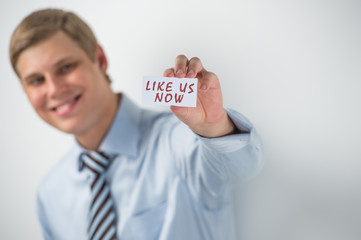 """Handsome businessman showing """"like us now"""" text on a business ca"""