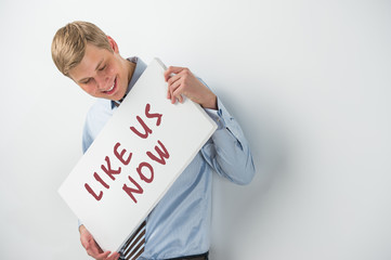 "Handsome businessman showing ""like us now"" text on a billboard"