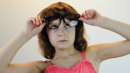 child plays with glasses and makes faces