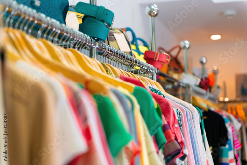 Variety of clothes hanging on rack
