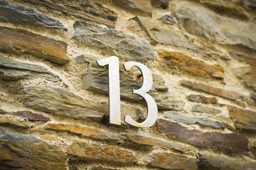 Thirteen on a stone wall