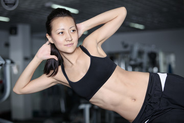 Woman at the gym doing exercises to strengthen abdominal muscles