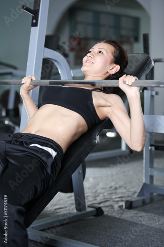 The girl is engaged in the gym on bench and raises the weight