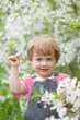 baby girl in  blossoming garden