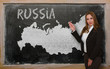 Teacher showing map of russia on blackboard