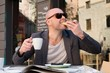 MIddle-aged man enjoying coffee with piece of cake in street caf