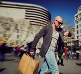 Middle-aged man with shopping bag in a hurry