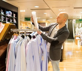 Middle-aged man choosing shirts in a shopping mall