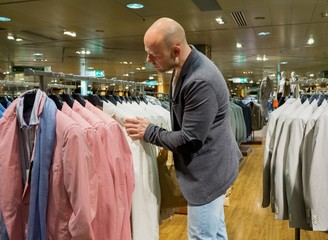 Middle-aged man choosing clothes in a shopping mall