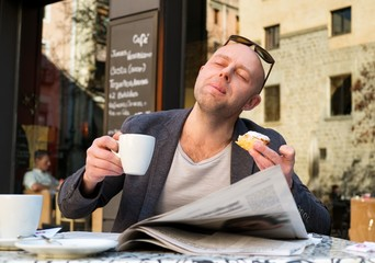 MIddle-aged man enjoying coffee with piece of cake