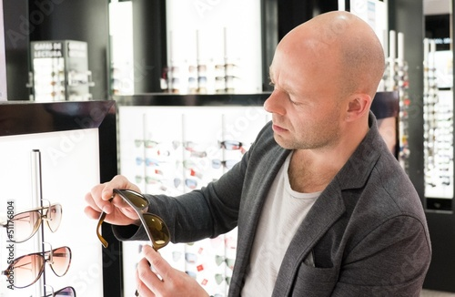 Middle-aged man choosing sunglasses in a shop