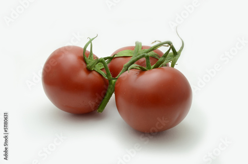 three fresh tomatoes with green leaves