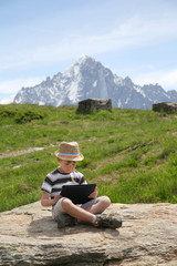 Boy with tablet PC on top of mountain