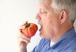 senior man eating big tomato