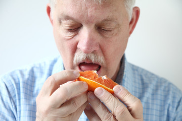 older man eating orange