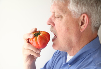 senior man eating big tomato
