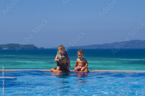 young happy mother and children enjoying vacation in swimming po
