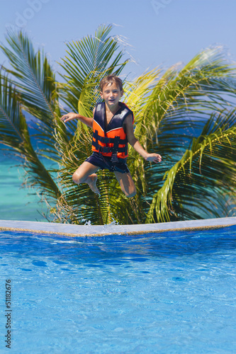 young happy boy jumping in swimming pool on tropical background
