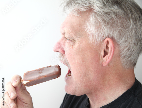 senior man with ice cream bar profile view