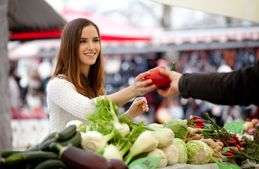 Farmer passing young woman a red pepper at the market