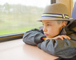 Boy rides on a train and looking out the window.