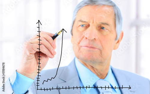 Businessman in age, draws a graph.