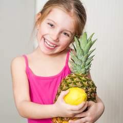 little girl with a pineapple and lemon