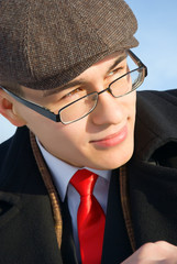 A young man in classic clothes and glasses.