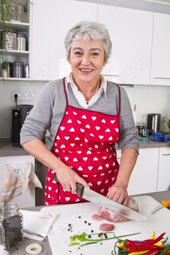 Ältere Frau schneidet Fleisch in der Küche