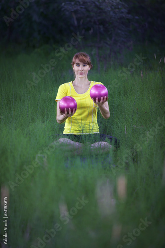 woman  in yoga position, raising   silver fitness balls