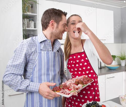 Verliebtes junges Paar in der Küche beim Essen